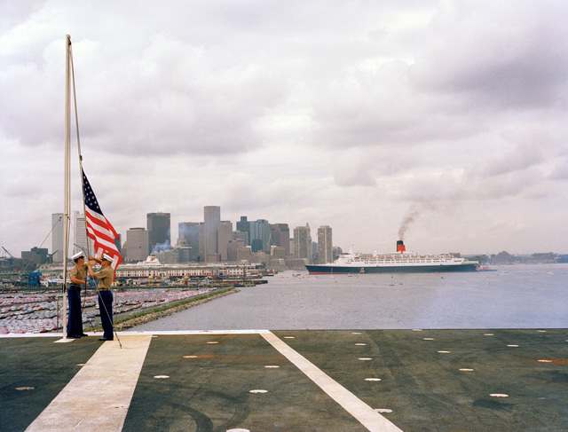 Marines on board the aircraft carrier USS JOHN F. KENNEDY (CV 67) shift the colors as the ship prepares to leave port.  The RMS QUEEN ELIZABETH II and the city of Boston are in the background