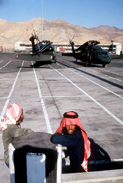 Jordanian dock workers relax as they watch the offloading of UH-60 Blackhawk helicopters and other equipment which will be used during SHADOW HAWK, the segment of the multiservice Exercise BIRGHT STAR '87 that tests joint Jordan-US operations