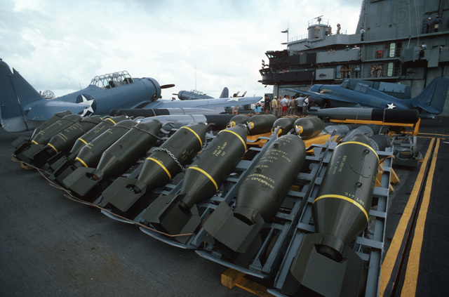 "A line of World War II-era bombs are staged on the flight deck of the training aircraft carrier USS LEXINGTON (AVT 16) during filming of the ABC-TV movie ""War and Remembrance."" An SNJ Texan aircraft, left and an F4F Wildcat aircraft are in the background"