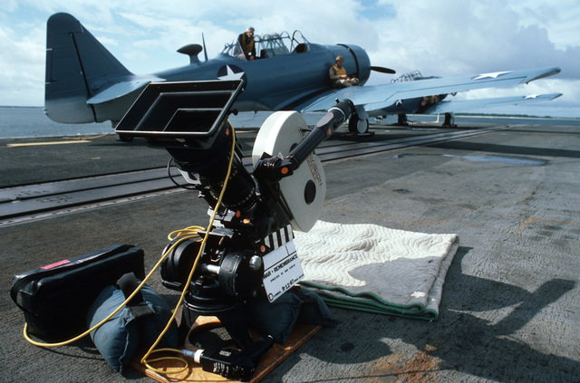 "A motion picture camera rests on the flight deck during filming of the ABC-TV movie ""War and Remembrance. An SNJ Texan aircraft is in the background"