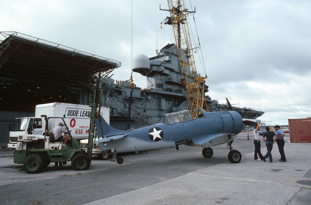 "An SNJ Texan aircraft is attached to a crane to be lifted onto the deck of the training aircraft carrier USS LEXINGTON (AVT 16) during filming of the ABC-TV movie ""War and Remembrance."""