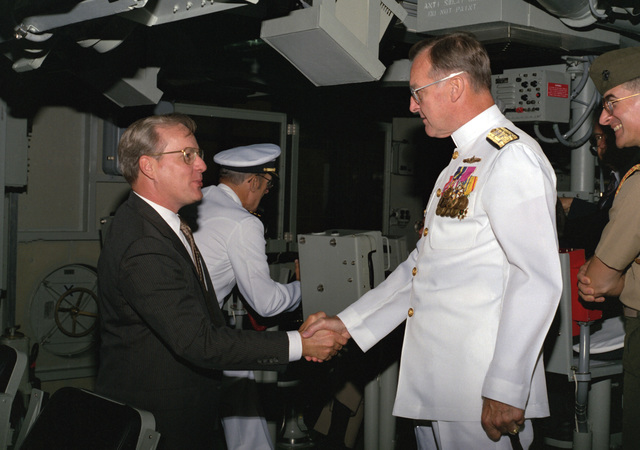 Lawrence Garett III, under secretary of the Navy, greets VADM William H. Rowden, commander, Naval Sea Systems Command, aboard the mine countermeasures ship USS AVENGER (MCM-1) after the ship's commissioning