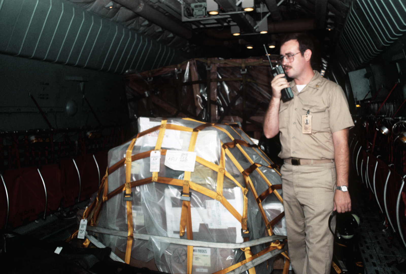CHIEF Cryptologic Technician (CTC) Arnold D. Collins radios a message from the cargo bay of a C-141B Starlifter aircraft that the Armed Forces Courier Station shipment has arrived