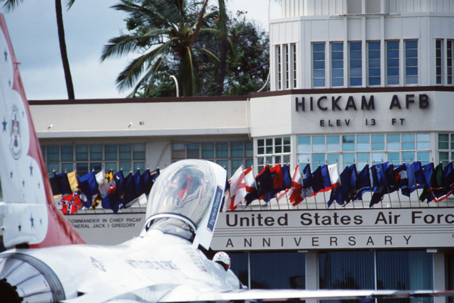 State flags decorate the operations building during an open house air show.  An Air Force Thunderbird Flight Demonstration Team F-16 Fighting Falcon aircraft is in the foreground