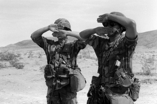 Private First Class (PFC) Jesse and SPECIALIST Fourth Class (SPC) Jose practice arm and hand signals at the National Training Center