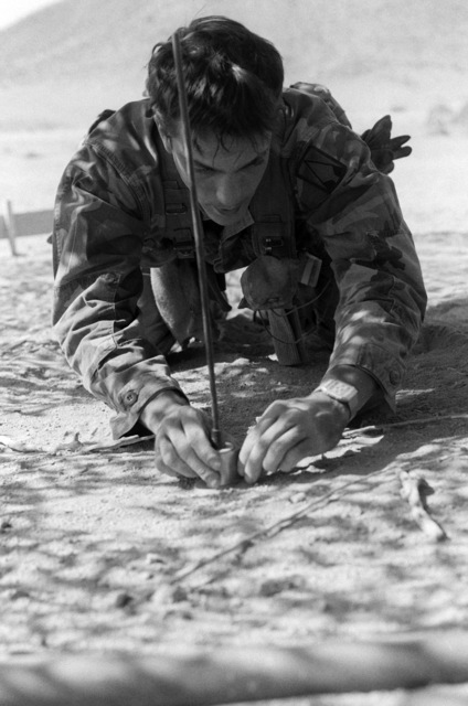 Private First Class (PFC) Morton sets up a booby-trap during an exercise at the National Training Center
