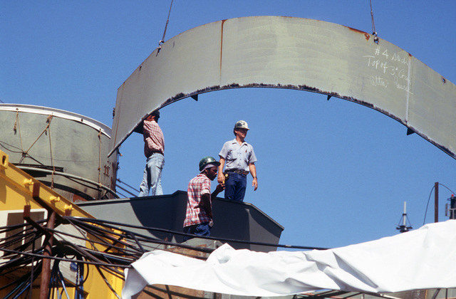 Shipyard workers mount steel plating aboard the battleship USS WISCONSIN (BB 64). The ship is undergoing overhaul by Ingalls Shipbuilding and is 50 percent complete