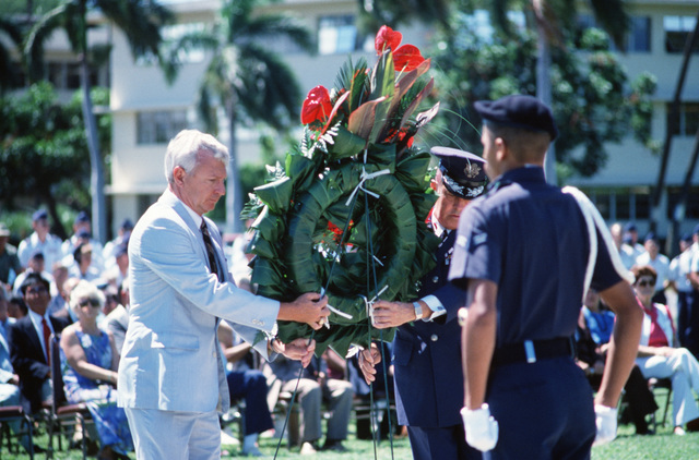 Edward C. Aldridge, Secretary of the Air Force, and General (GEN) Jack I. Gregory, Commander-In-CHIEF, Pacific Air Forces, place a wreath at the base of the flagpole during a ceremony in remembrance of American prisoners of war and those listed as missing