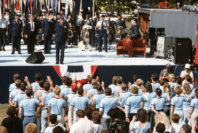 """General (GEN) Alfred G. Hansen, commander, Air Force Logistics Command, enlists a group of people into the Air Force as part of a ceremony during the""""Festival of Flight,""""an Air Force 40th anniversary celebration"""
