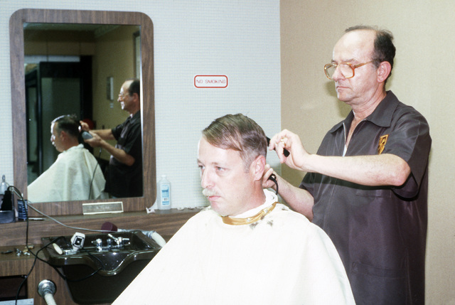 A Soldier gets a haircut at the barbershop at the Post Exchange Mini Mall