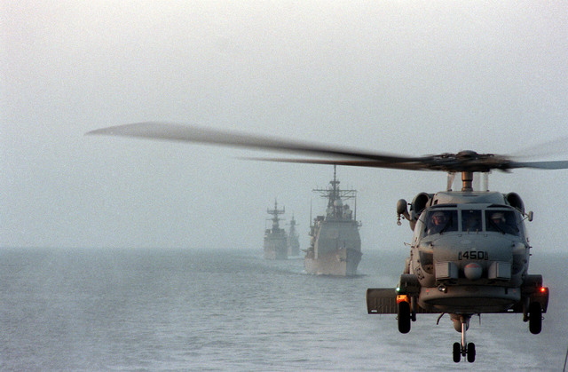 An SH-60B Seahawk helicopter conducts anti-submarine warfare operations for the aircraft carrier USS SARATOGA (CV-60) battle group. The guided missile cruiser USS TICONDEROGA (CG-47) and other unidentified ships are in the background