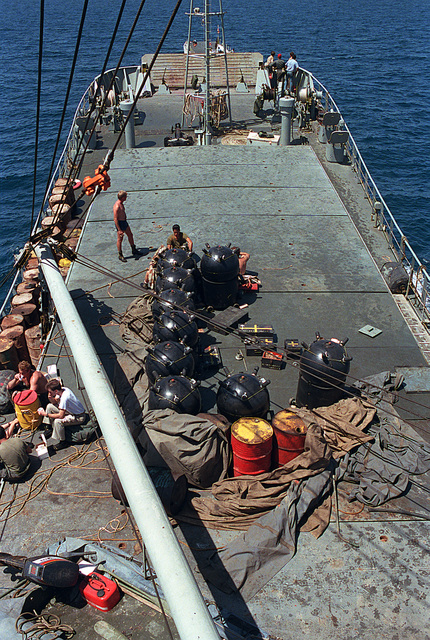 Contact mines partially covered by a tarpaulin on the deck of the captured Iranian mine-laying ship TRAN AJR