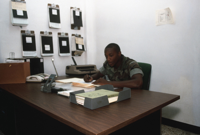 Lance Corporal (LCPL) Johnny W. Hamilton looks over records that will be sent to Kansas City and added to the Marine Corps computer system. Hamilton is part of the Marine Corps Security Force Company