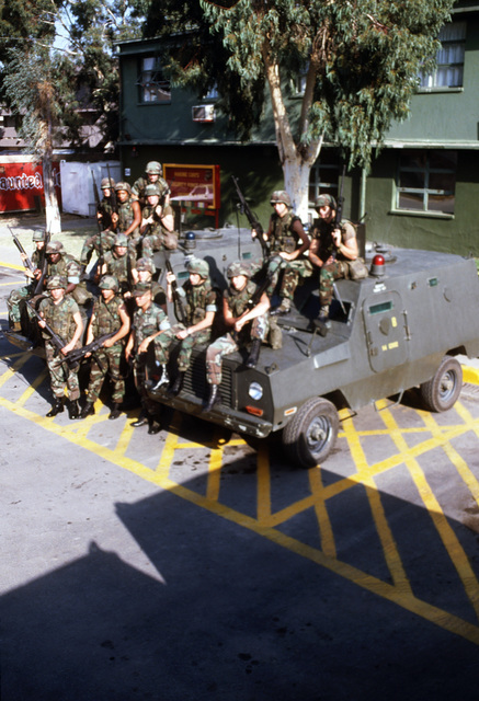 Members of the Marine Corps Security Force Company pose for a group photo on their Cadillac Gage Commando Ranger vehicles