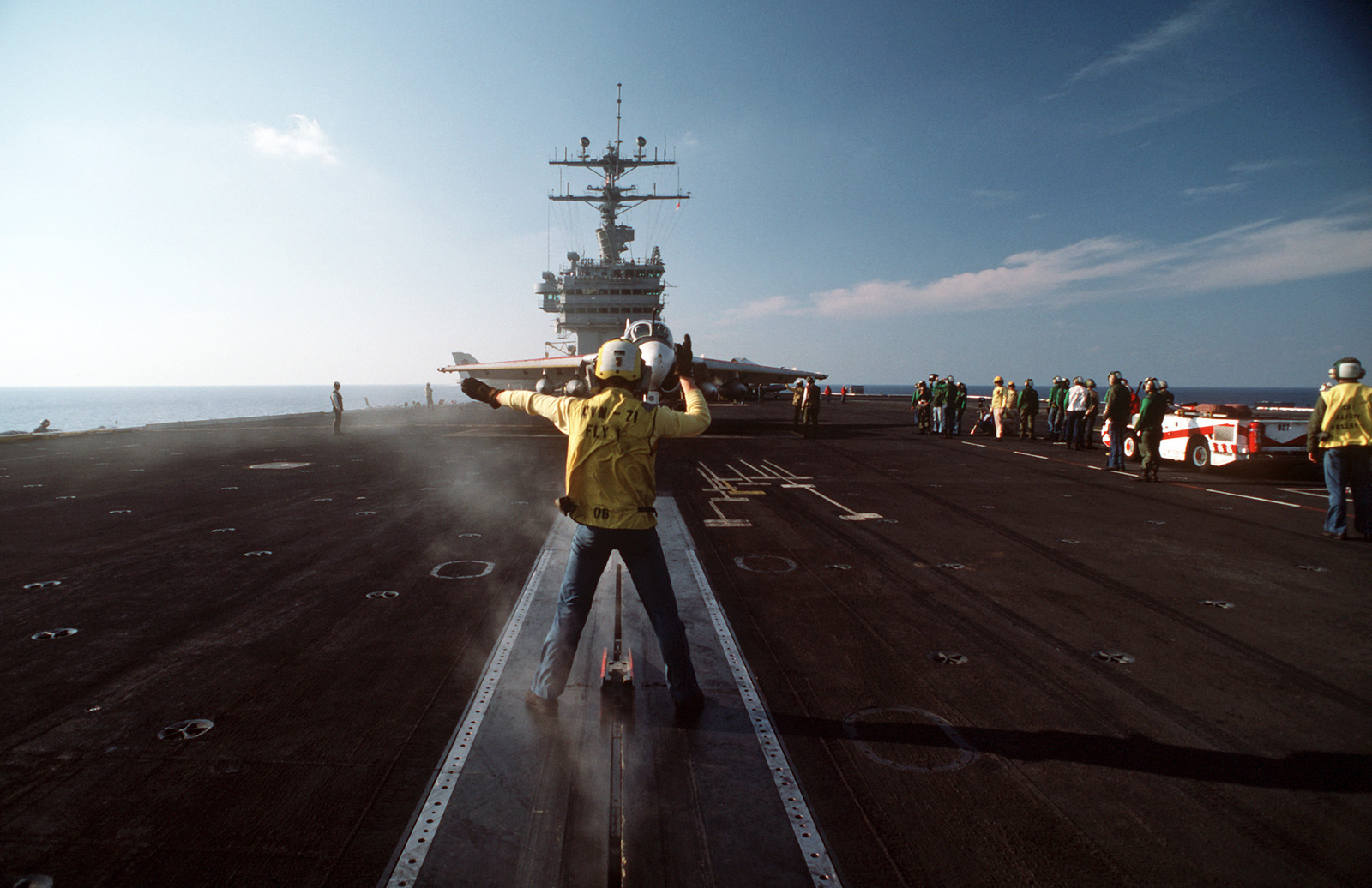 A plane director signals instructions to the pilot of an A-6E Intruder aircraft aboard the nuclear-powered aircraft carrier USS THEODORE ROOSEVELT (CVN 71)