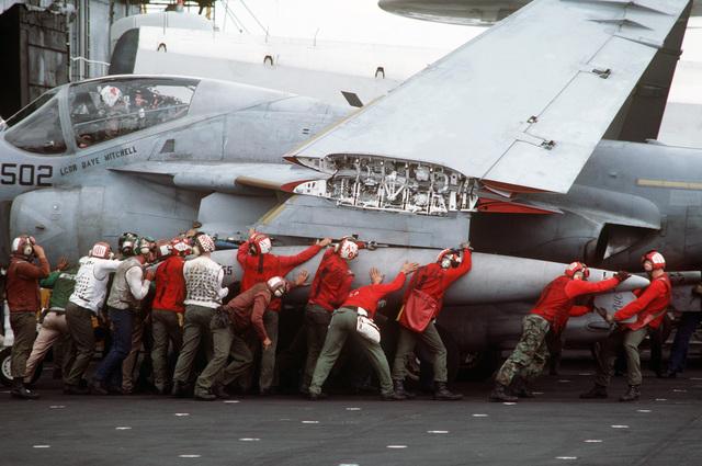 Flight deck crewmen maneuver an A-6E Intruder aircraft on the flight deck of a US Navy aircraft carrier