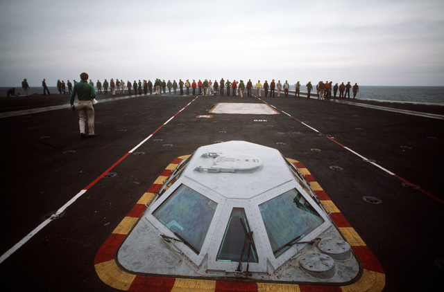 Flight deck crewmen stage a foreign object damage walk-down on the flight deck of the nuclear-powered aircraft carrier USS THEODORE ROOSEVELT (CVN 71). In the foreground is the integrated catapult control station