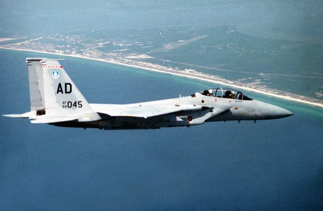 Shot of an F-15 Eagle aircraft in flight near a coastline