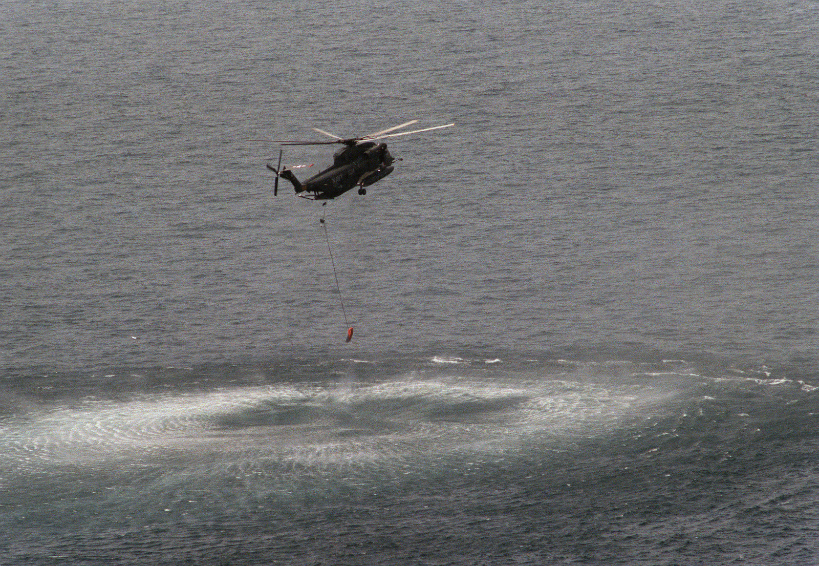 A Helicopter Mine Countermeasures Squadron 14 (HM 14) RH-53D Sea Stallion helicopter retrieves a float from the water during a minesweeping operation