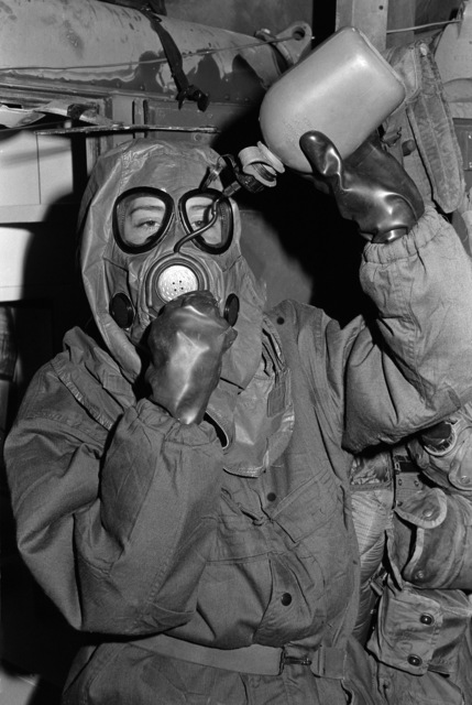 A Marine demonstrates the procedure for drinking from a canteen while in mission oriented protective posture, level 4 (MOPP 4) nuclear-biological-chemical (NBC) warfare gear