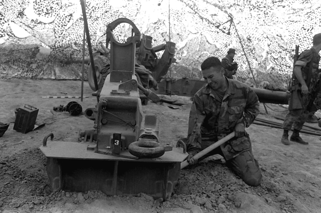 A Marine from Co. K, 4th Bn., 12th Marines, digs in the ground to bury the spade of the M-198 155mm howitzer before the gun can be fired during Operation Bear Hunt '88