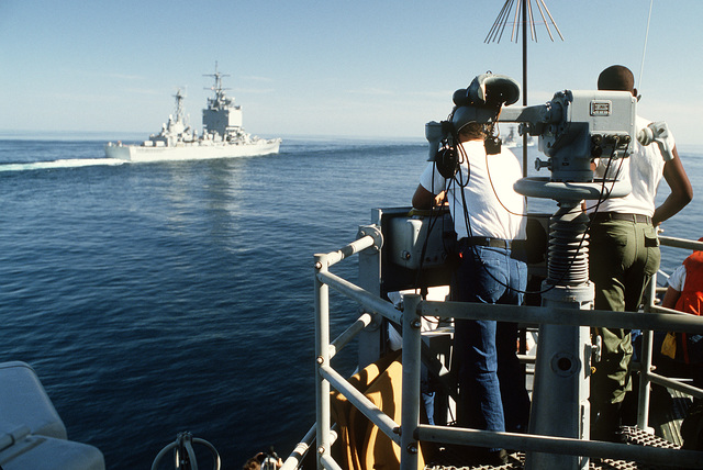 A signalman seaman aboard the guided missile frigate USS FORD (FFG-54) sends a flashing light message to the nuclear-powered guided missile cruiser USS LONG BEACH (CGN-9) while both ships are underway. The ships are participating in a reflagged tanker escort operation