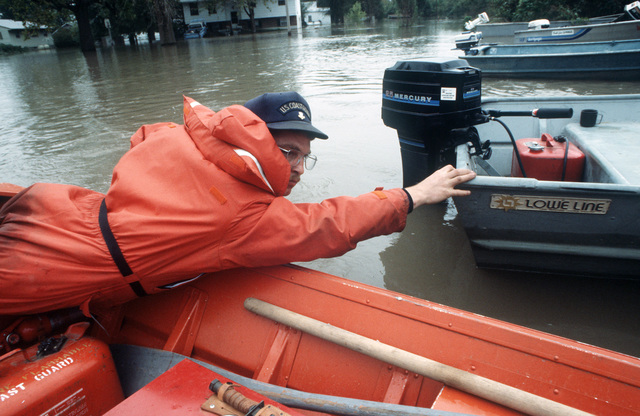 A US Coast Guardsman helps land a boat during flood rescue operations.  Flood waters from the Missouri and Mississippi Rivers invaded river towns throughout Missouri and Illinois and caused a state of emergency which required the response of the Missouri