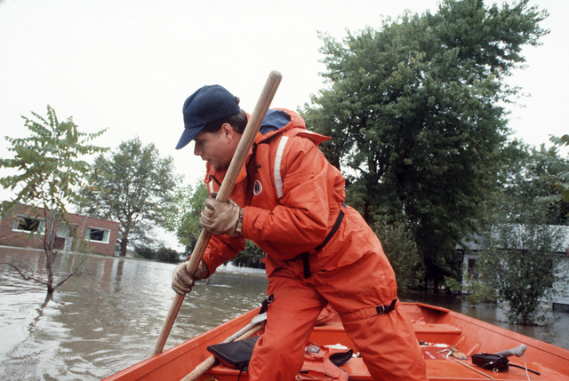 A US Coast Guardsman uses a pole to check water depth during flood rescue operations.  Flood waters from the Missouri and Mississippi Rivers invaded river towns throughout Missouri and Illinois and caused a state of emergency which required the response o