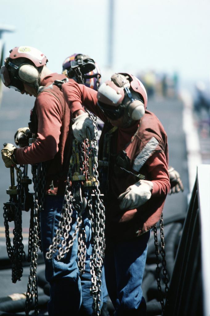 Aircraft handling crewmen sort through aircraft tie-down chains during flight operations aboard the nuclear-powered aircraft carrier USS DWIGHT D. EISENHOWER (CVN 69)