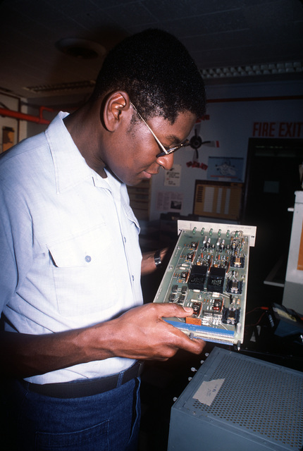 Aviation Electronics Technician 1ST Class (AT1) Cornelius Stripling of Patrol Squadron 68 (VP-68) inspects a circuit board from a P-3B Orion aircraft