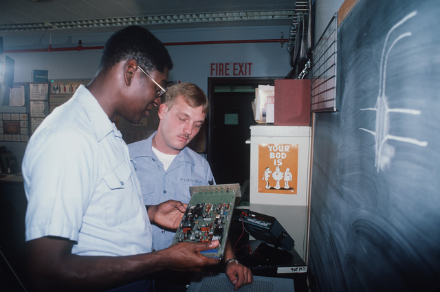 Aviation Electronics Technician 1ST Class (AT1) Cornelius Stripling shows a circuit board from a Patrol Squadron 68 (VP-68) P-3 Orion aircraft to Aviation Anti-submarine Warfare Technician 3rd Class John Ferguson