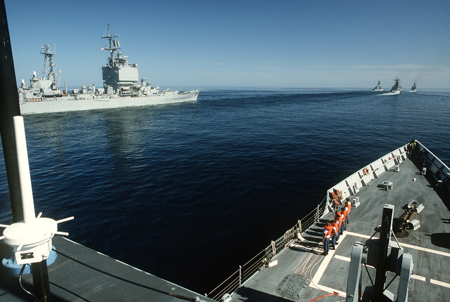 Highline party members stand by onboard the guided missile frigate USS FORD (FFG-54). The nuclear-powered guided missile cruiser USS LONG BEACH (CGN-9) is underway off the port bow of the FORD. The ships are participating in an reflagged tanker escort operation