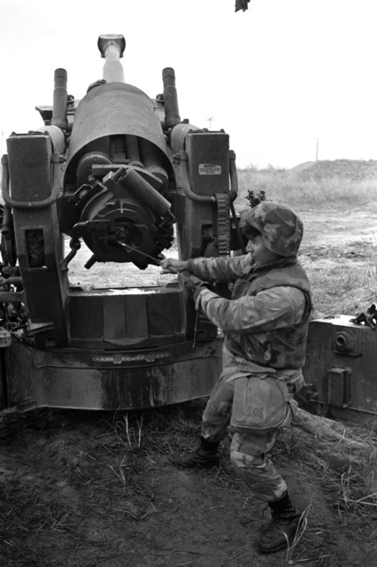 Lance Corporal (LCPL) Danny Cruz of Company L, 4th Battalion, 12th Marines, pulls the lanyard to fire his M198 155 mm Howitzer during a regimental firing exercise during Operation BEAR HUNT'88
