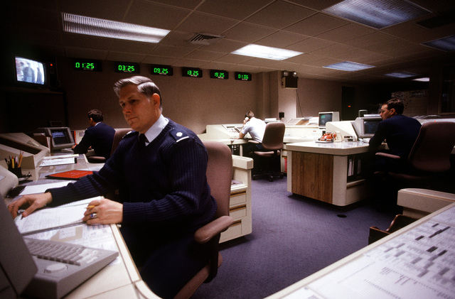 MAC senior staff personnel gather data for briefings in the offices adjoining the command post for the Military Airlift Command (MAC) headquarters at Scott Air Force Base, Illinois. Exact Date Shot Unknown