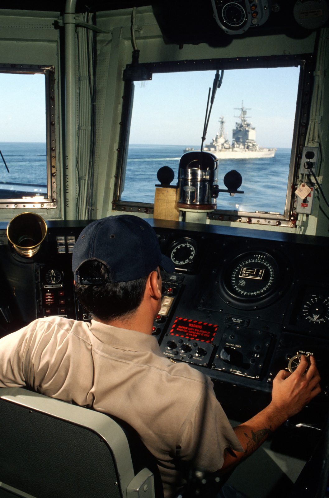 Persian Gulf. A chief quartermaster mans the helm of the guided missile frigate USS FORD (FFG 54) as the ship approaches the nuclear-powered guided missile cruiser USS LONG BEACH (CGN 9). The FORD is escorting reflagged tankers through the Gulf