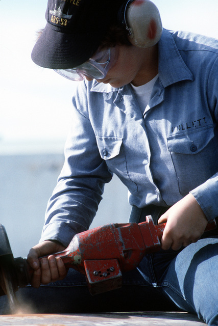 SEAMAN Susan Collett, a crewman from the salvage ship USS GRAPPLE (ARS-53), uses a power grinder to remove rust from the ocean minesweeper USS FEARLESS (MSO-442). The FEARLESS is one of three minesweepers being towed to the Persian Gulf by the GRAPPLE to support U.S. Navy escort operations