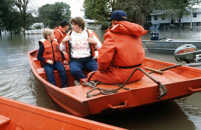 U.S. Coast Guardsmen transport townspeople to safety during flood rescue operations. Flood waters from the Missouri and Mississippi Rivers invaded river towns throughout Missouri and Illinois and caused a state of emergency which required the response of