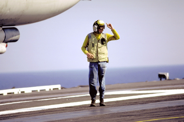 A flight deck crew member signals to another crew member during flight operations aboard the nuclear-powered aircraft carrier USS DWIGHT D. EISENHOWER (CVN-69). The EISENHOWER is participating in a week of carrier qualifications testing off the Virginia Capes