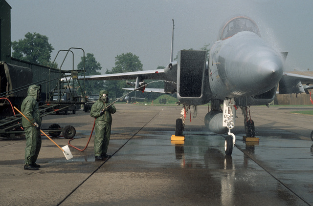 A member of the 33rd Equipment Maintenance Squadron decontaminates a 58th Tactical Fighter Squadron F-15 Eagle aircraft with a soapy water during a chemical exercise.  He is participating in Exercise CORNET PHASER, a NATO rapid deployment exercise conducted under simulated wartime conditions