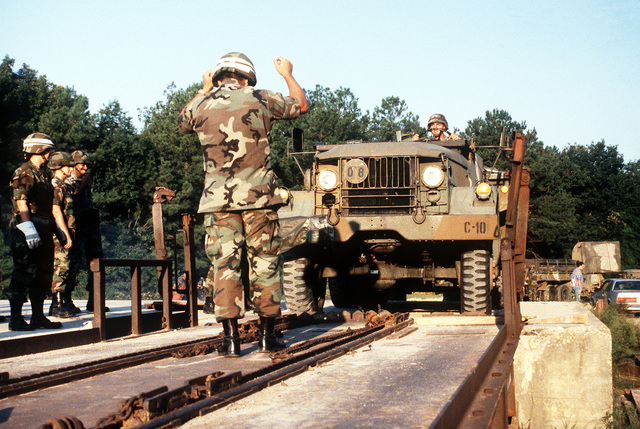 A member of the 3rd Battalion, 68th Air Defense Artillery, directs an M-35A2 truck onto a railcar during a joint Air Force and Army air-drop/air-assault exercise