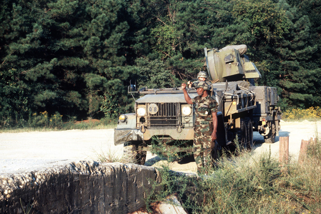 A member of the 3rd Battalion, 68th Air Defense Artillery, directs an M35A2 truck onto a railway loading platform during a joint Air Force and Army air-drop/air-assault exercise