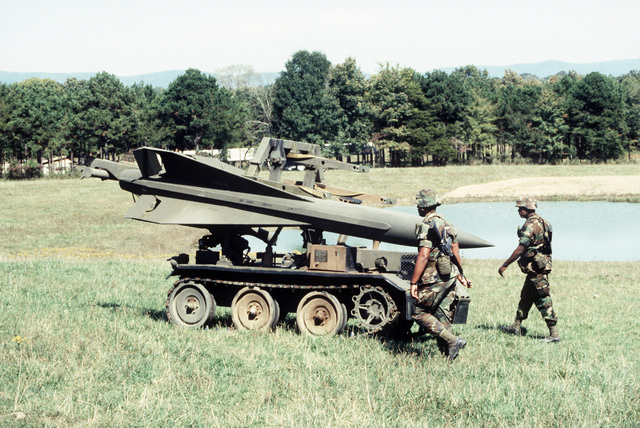 An XM-501E2 loader/transporter carries an MIM-23 Hawk missile across a field during a joint Air Force and Army air-drop/air-assault exercise