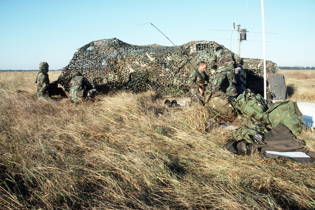 Members of the 1ST Battalion, 58th Aviation Regiment, use camouflage netting to cover their radio base during a joint Air Force and Army air-drop/air-assault exercise