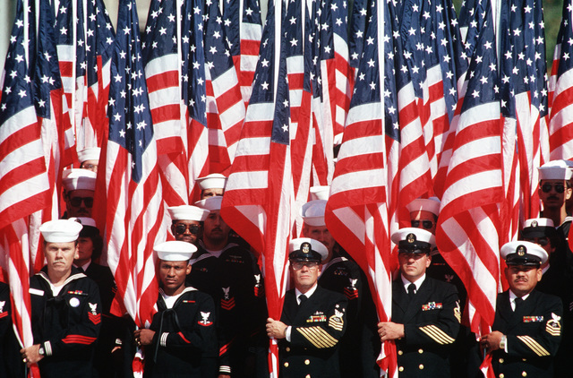 Navy personnel hold a bevy of US flags during the dedication ceremonies for the US Navy Memorial