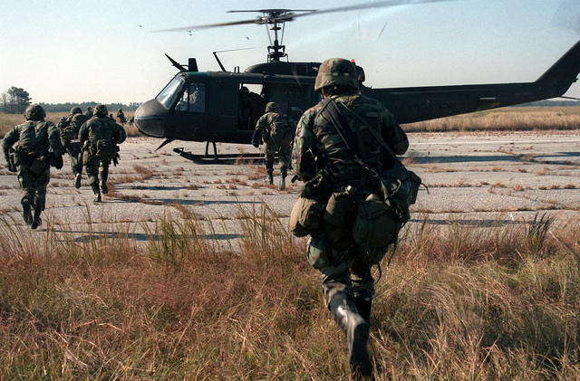 Soldiers of Co. C, 1ST Bn., 505th Parachute Infantry Regt., run toward a waiting UH-1 Iroquois helicopter during a joint Air Force and Army air-drop/air-assault exercise