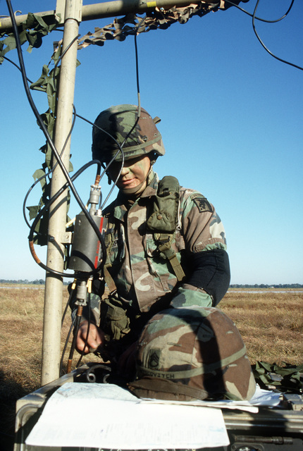 SPECIALIST (SPC) John Murphy, Company B, 1ST Battalion, 58th Aviation Regiment, covers a radio antenna with camouflage during a joint Air Force and Army air-drop/air-assault exercise
