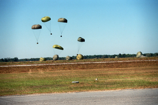Supplies dropped from a C-141B Starlifter aircraft descend to the ground during a joint Air Force and Army air-drop/air-assault exercise