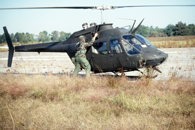 The crew chief of an OH-58 Kiowa scout helicopter performs a preflight check during a joint Air Force and Army air-drop/air-assault exercise
