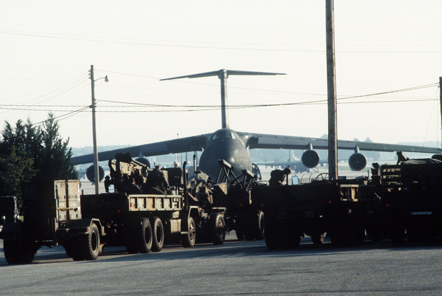 Vehicles of the 3rd Battalion, 68th Air Defense Artillery, await loading aboard a C-5A Galaxy aircraft during a joint Air Force and Army air-drop/air-assault exercise