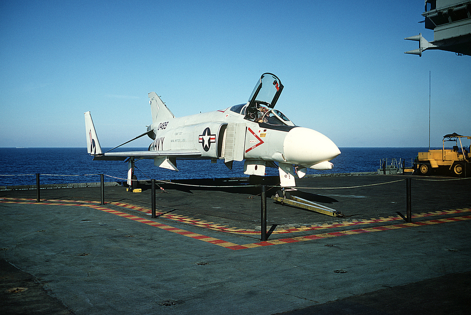 A pilot sits in the cockpit of a Naval Air Test Center F-4J Phantom II aircraft parked on an elevator aboard the attack aircraft carrier USS AMERICA (CVA-66)